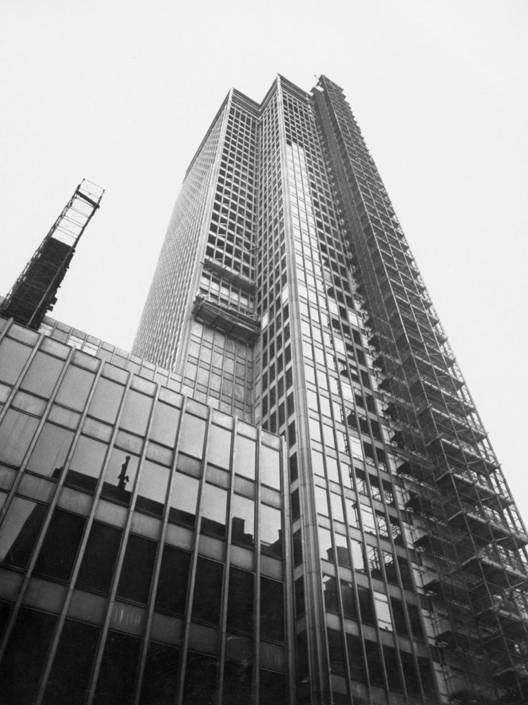 Mies' Manhattan Tower, the 38-story Seagram Building under construction on Park Avenue, is flanked by elevator shafts for lifting building materials to top. In rare switch for Mies, indented area at left has marble walls, not glass.
