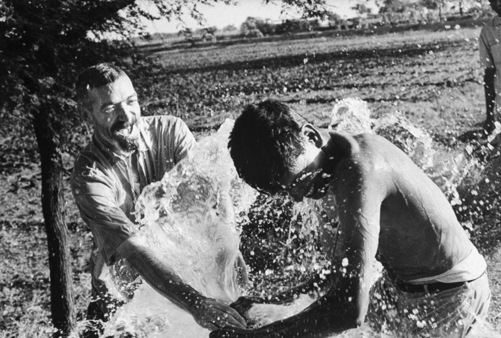 Missionary priest Vincent Ferrer (left) and assistant Mahadev (right) splash in water from a new well on a model farm in India in 1968.