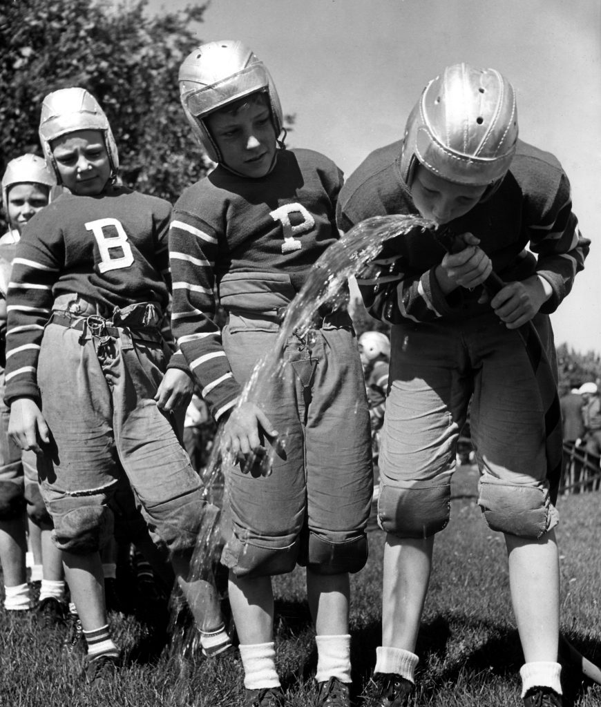 Thirsty young football players drink water from a garden hose in Denver, Colorado, in 1939.