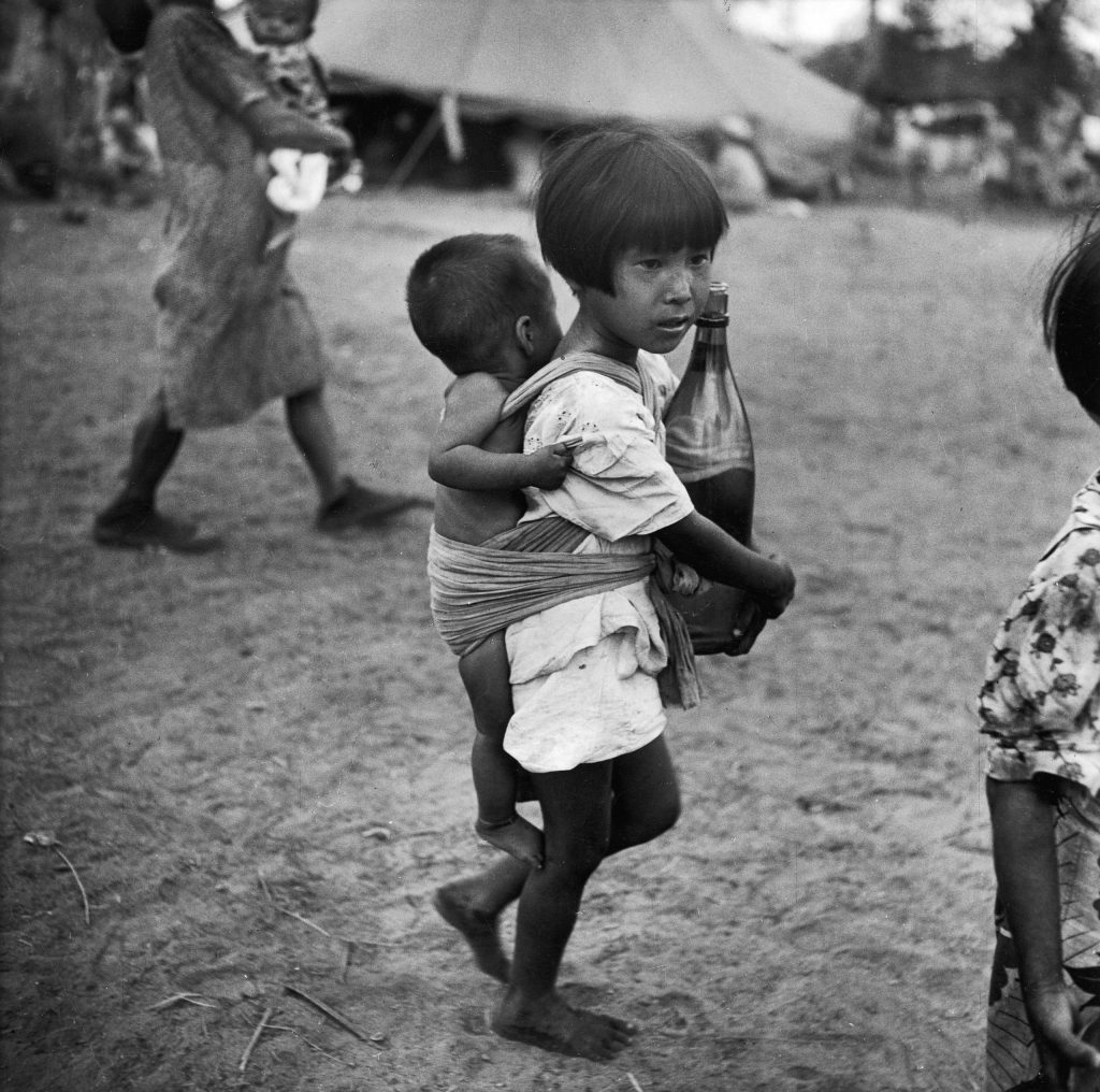 A girl in a village on Saipan (Marianas Islands) carries a bottle of water in her arms and a baby on her back in 1944.