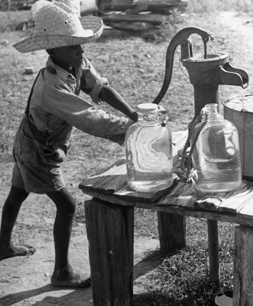 A sharecropper's son gets water from a pump on a farm in the Mississippi delta in 1937.