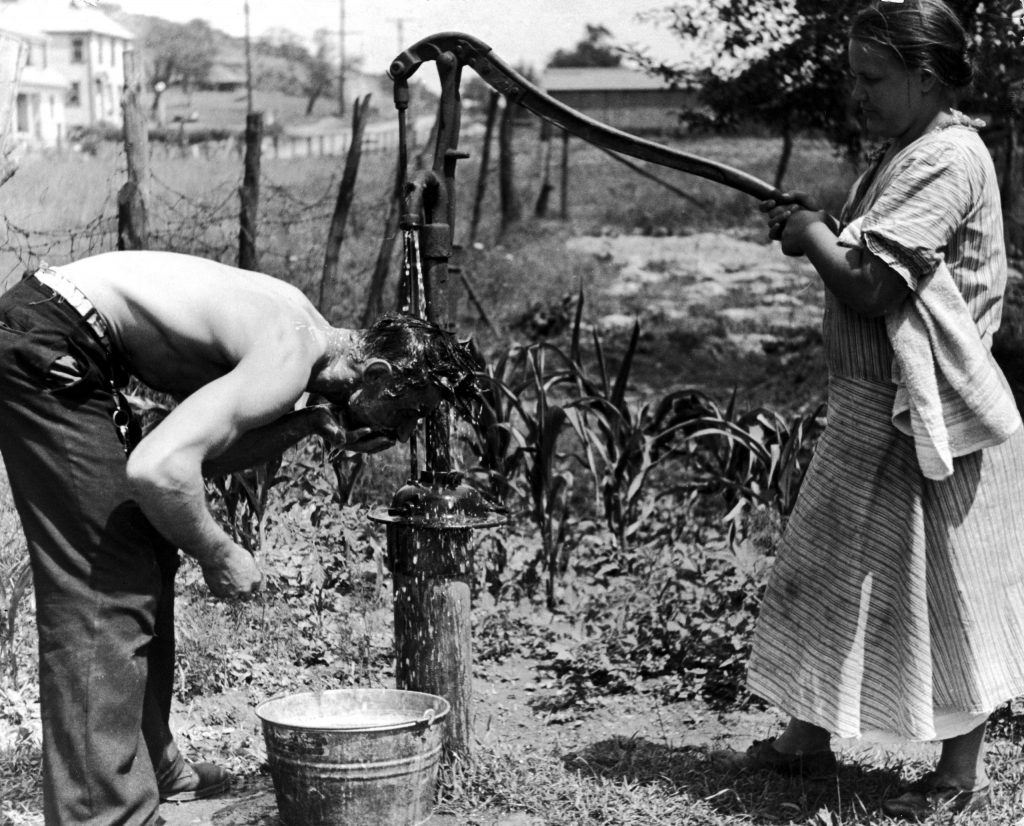 A steelworker in Aliquippa, Penn., washes up at an outdoor pump in 1936.