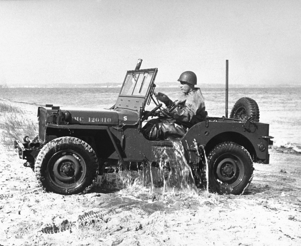 A soldier drives a Jeep out of the water in 1946.
