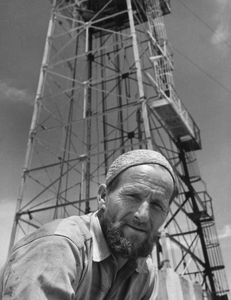 Jack Stovall, native of Texas, is an assistant driller. He has grown and Arabian-type beard, is wearing an Arabian-type cap. Many Americans become proficient at speaking Arabic.