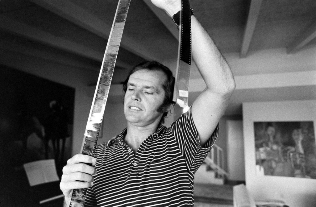 Jack Nicholson looks at film negatives at his home, Los Angeles, 1969.