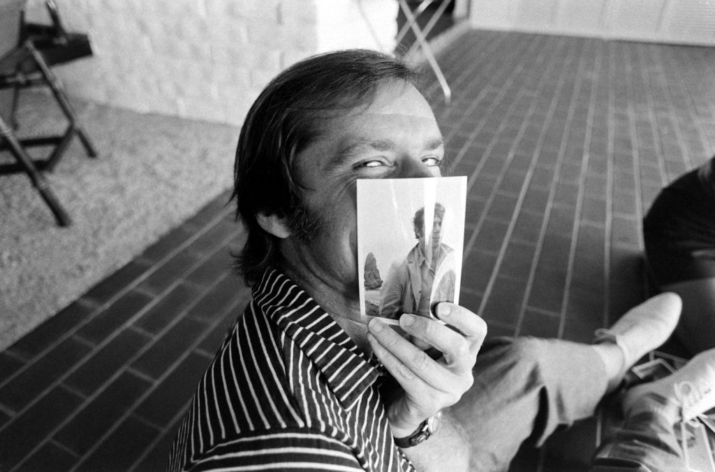 Jack Nicholson clowns around at his home with a picture of his friend, the film director Bob Rafelson, Los Angeles, 1969.