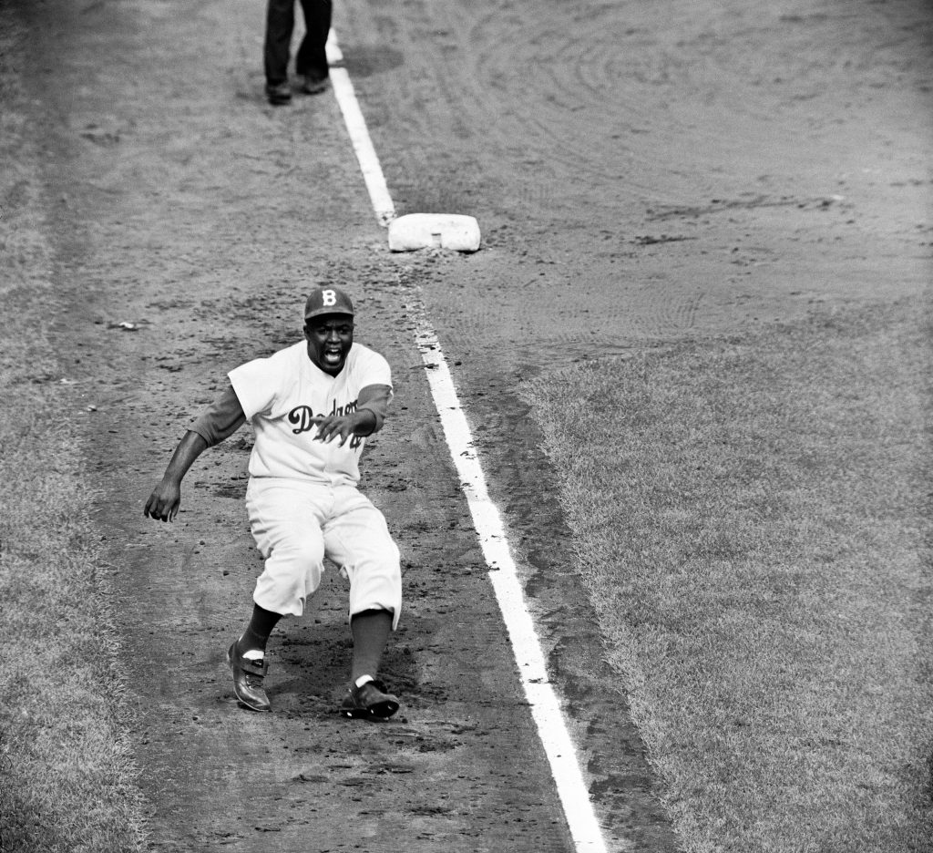 Hoping to distract Yankee catcher Yogi Berra and disrupt the pitcher, Bob Turley, Jackie Robinson dances off of third base during the third game of the 1955 World Series at Ebbets Field.