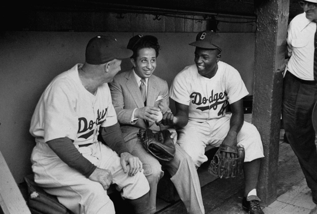 Jackie Robinson, Brooklyn manager Charlie Dressen and Iraq's King Faisal II chat in the dugout in 1952.