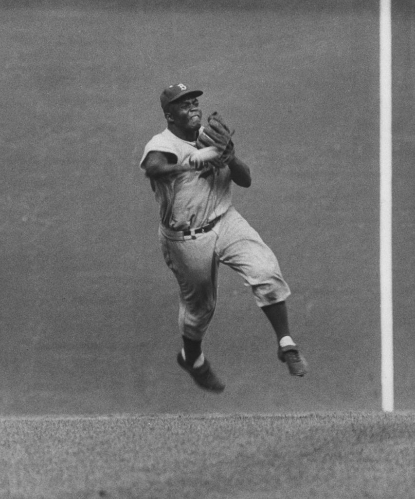 Jackie Robinson in action during game with the Giants, 1956