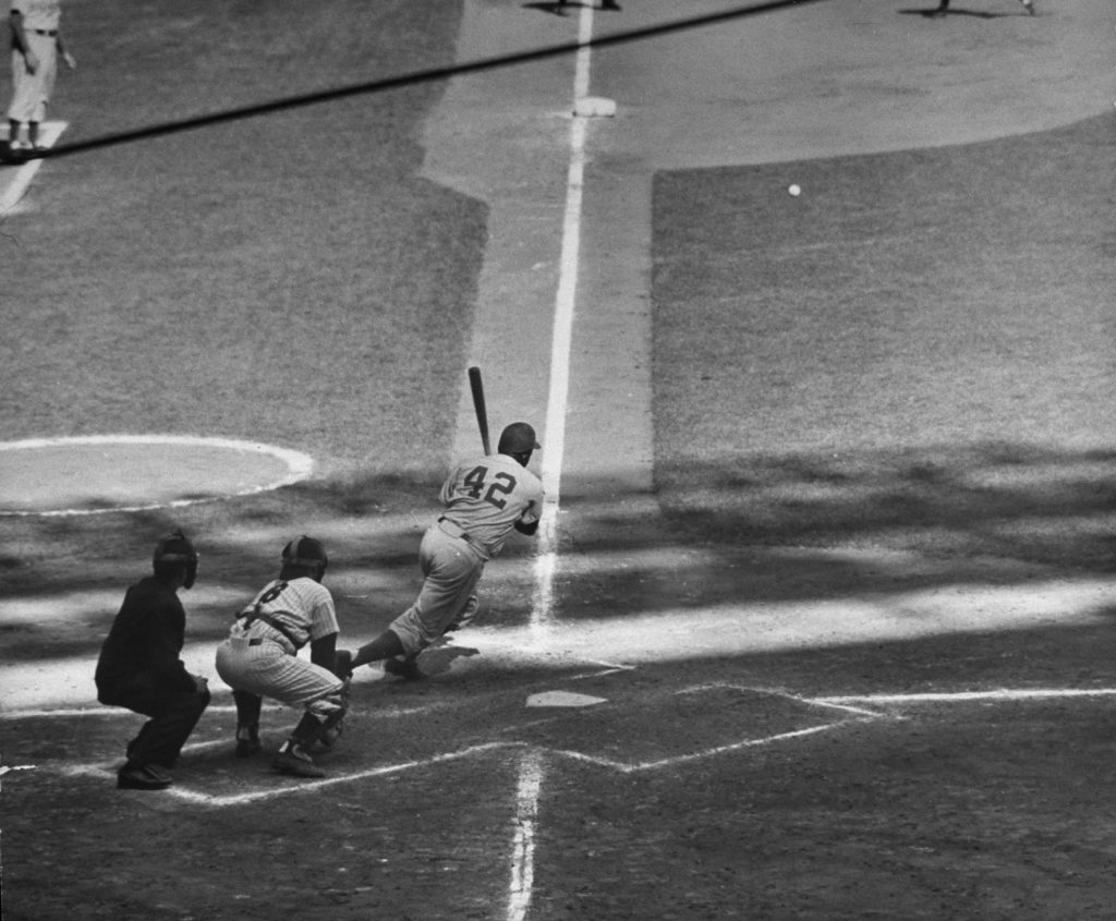 Jackie Robinson slashes a base hit during Game 6 of the 1955 World Series.