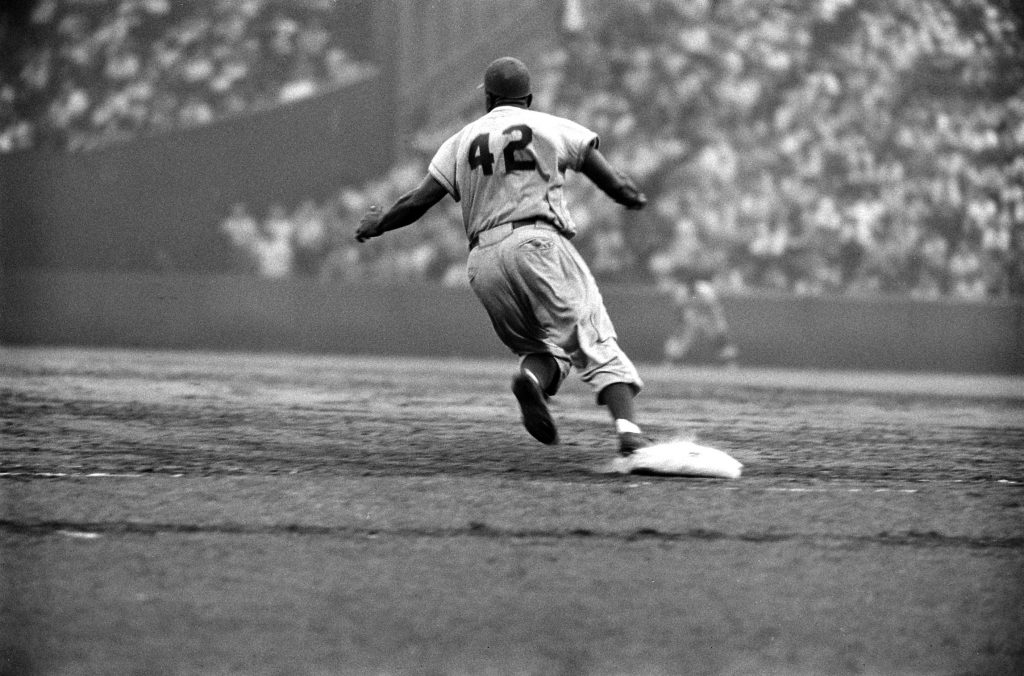 Jackie Robinson rounds first during a game against the Giants in 1956.
