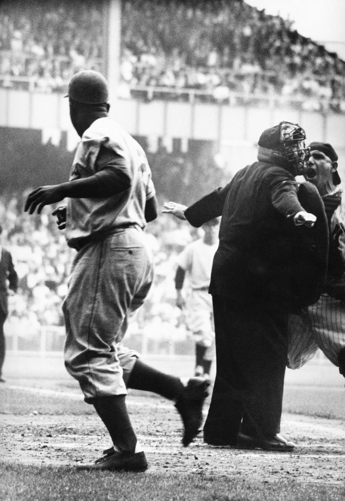 "Yogi Berra takes issue with the umpire's ""safe"" call after Jackie Robinson's electrifying steal of home in Game 1 of the 1955 World Series."