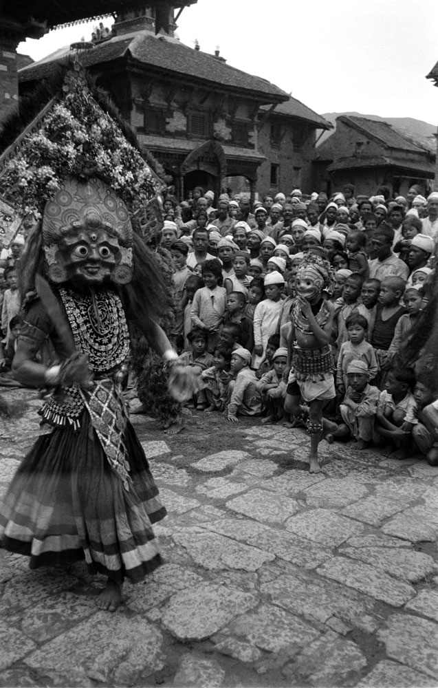 Getting ready for heroes, devil dancers prance in Temple Square, Nepal, 1953.