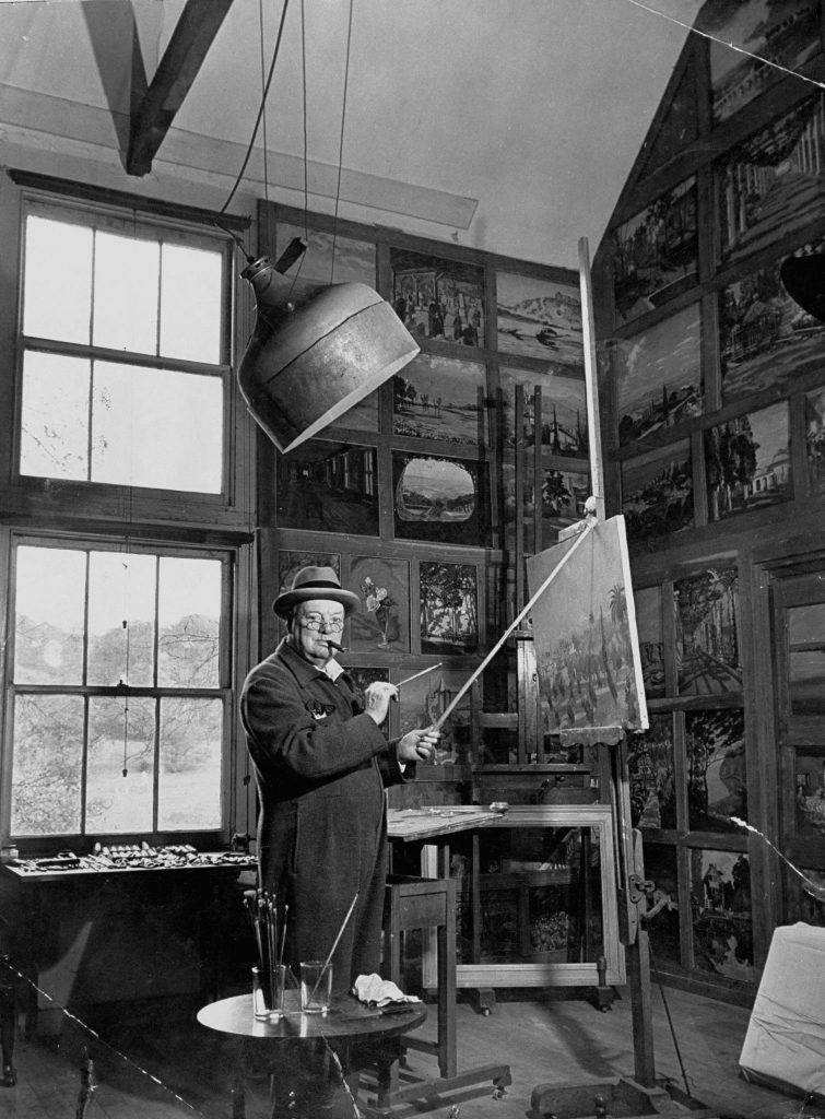 Winston Churchill stands in his studio at [his home] Chartwell, Kent, dressed in his RAF-blue siren suit, and peers over his spectacles at the camera while retouching one of his old landscapes.