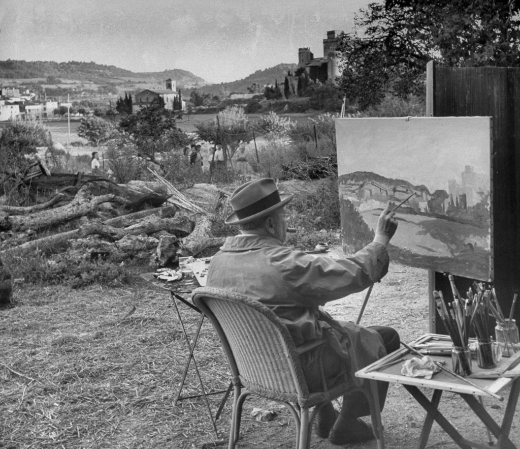 Winston Churchill at his easel painting and smoking a cigar near Aix-en-Provence, France.