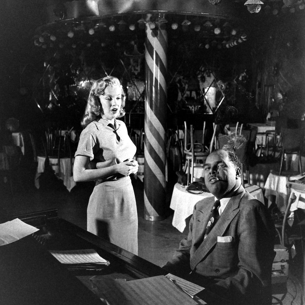 Marilyn Monroe, 22, takes singing lessons with bandleader Phil Moore at the famous West Hollywood nightclub, the Mocambo.
