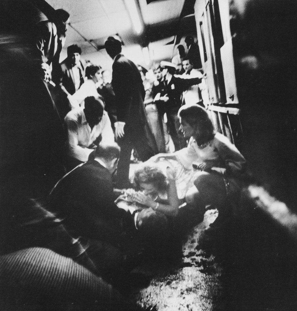 Mrs. Robert Kennedy, who had been walking with the senator, crouched over her dying husband, whispering to him as he lay on the floor. Beside her, waiting for the ambulance attendants to arrive, knelt her sister-in-law, Mrs. Stephen Smith and Dr. Ross Miller.
