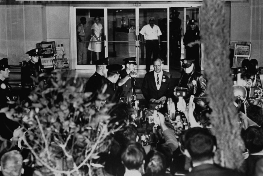 Aide to Sen. Robert Kennedy, Frank Mankiewicz (center, in suit and tie), prepares to address the media gathered outside the Hospital of the Good Samaritan, Los Angeles, June 5, 1968.