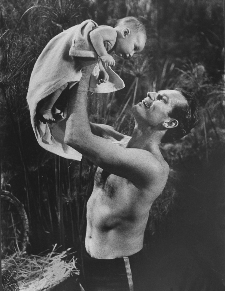 "Actor Charlton Heston lifting two-month-old son Fraser, who is portraying the baby Moses, into the air during filming of C.B. DeMille's ""The Ten Commandments."""