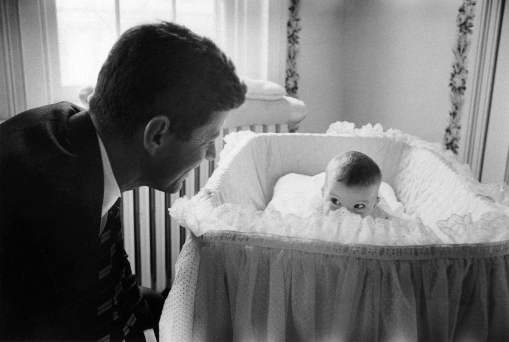 Senator John F. Kennedy plays peek-a-boo with daughter Caroline in 1958.