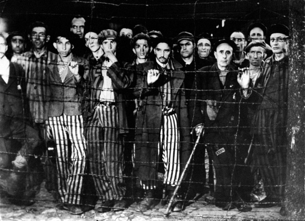 Buchenwald concentration camp prisoners stare in disbelief at their Allied liberators, April 1945.