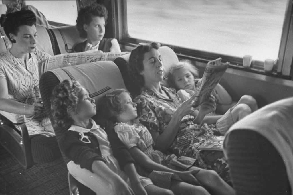 "A mother reads her children the comics while traveling on the ""El Capitan"" train between Chicago and Los Angeles, 1945."
