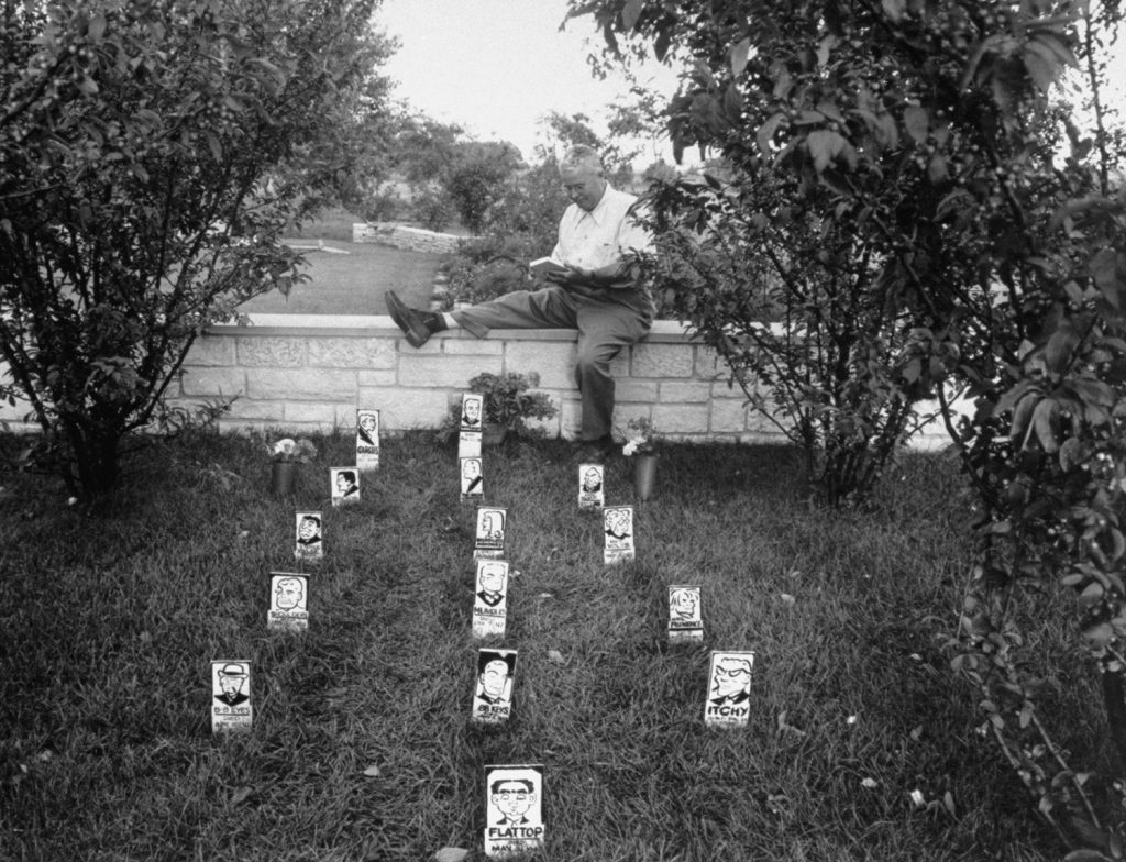 "Cartoonist Chester Gould sitting on wall beside cemetery where he ""buried"" vanquished villains from his ""Dick Tracy"" comic strip, 1949."