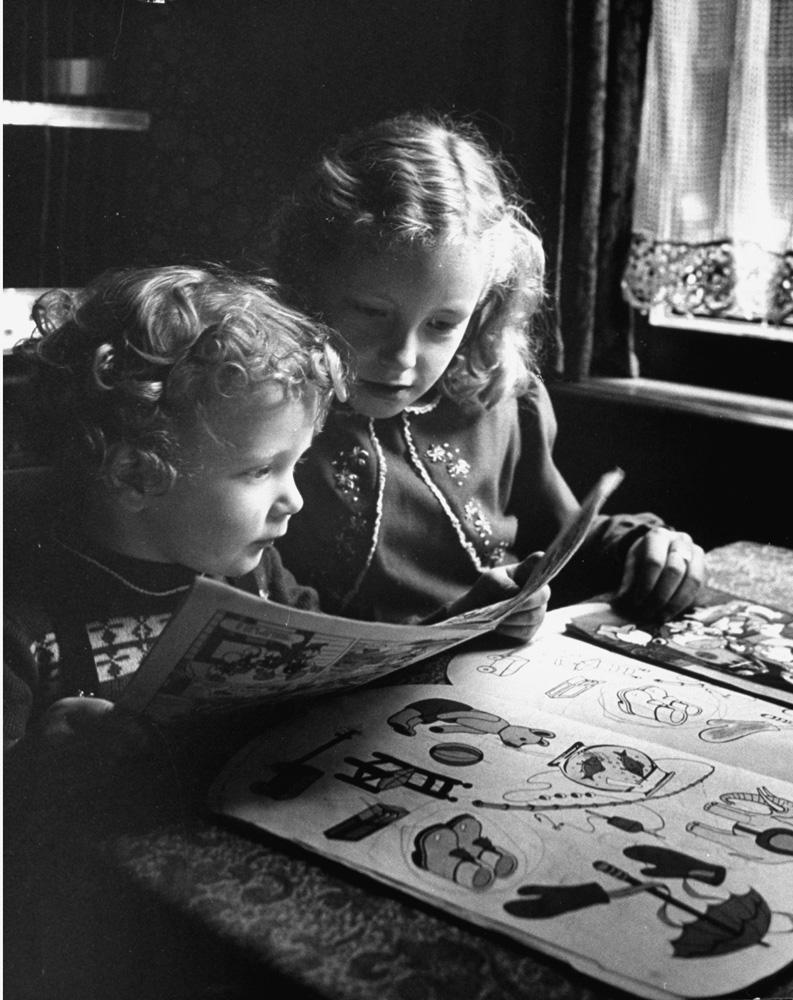 Two Dutch children read comic books in 1953, Netherlands.