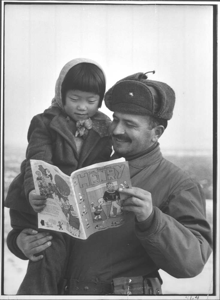 A Turkish soldier looks at an American comic book with a Korean girl during the Korean War, 1951.