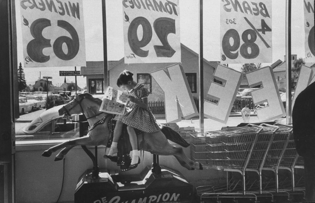 A young girl reads a comic book at an Anchorage, Alaska, supermarket in 1958.
