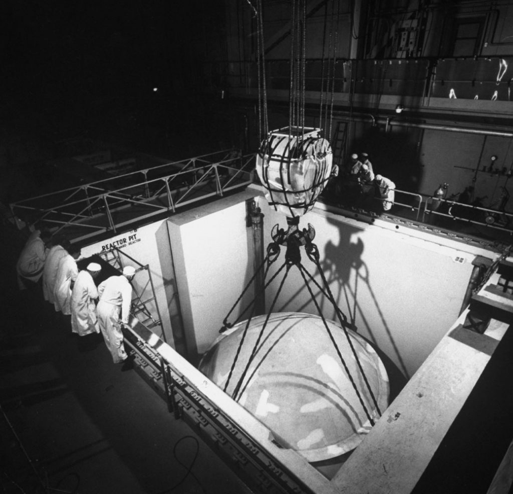 Reactor dome is lowered, by means of a huge crane, into the reactor pit of the under-construction Shippingport Atomic Power Station in Pennsylvania, 1957.