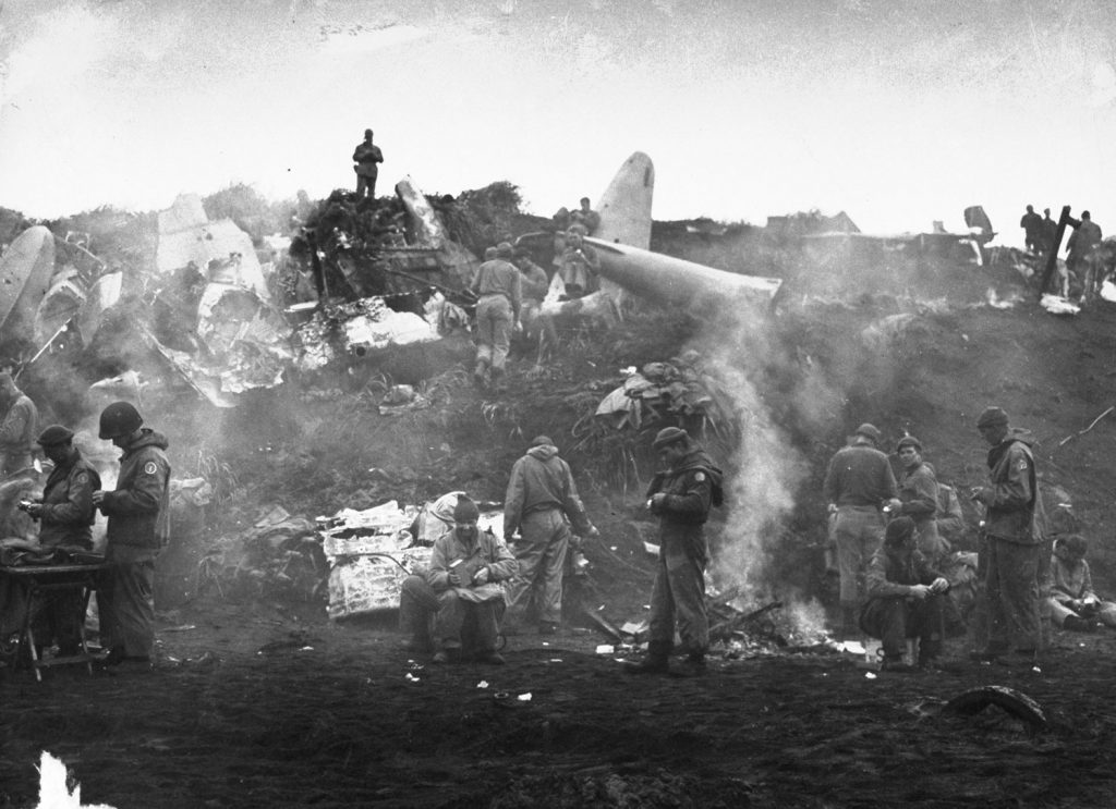 On the island of Kiska, men build fires near wrecked equipment and cook their meals, Alaska, 1943.