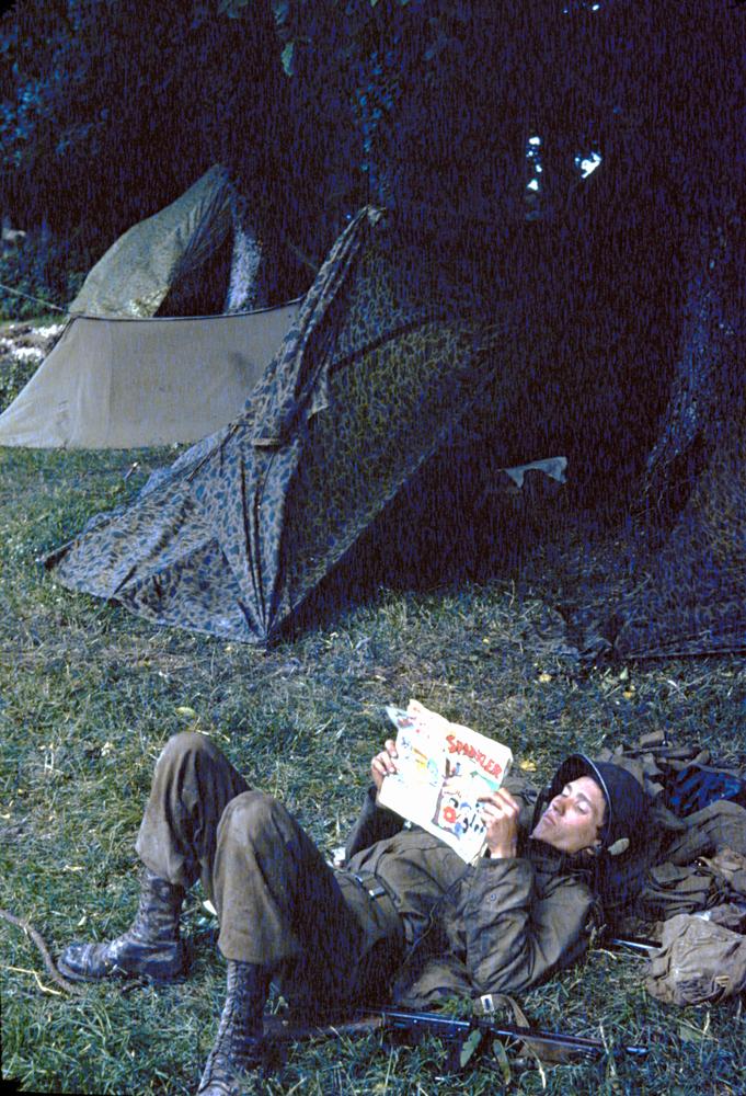 Private Ernest Dandou reads a comic book at paratrooper camp, Georgia, 1944.