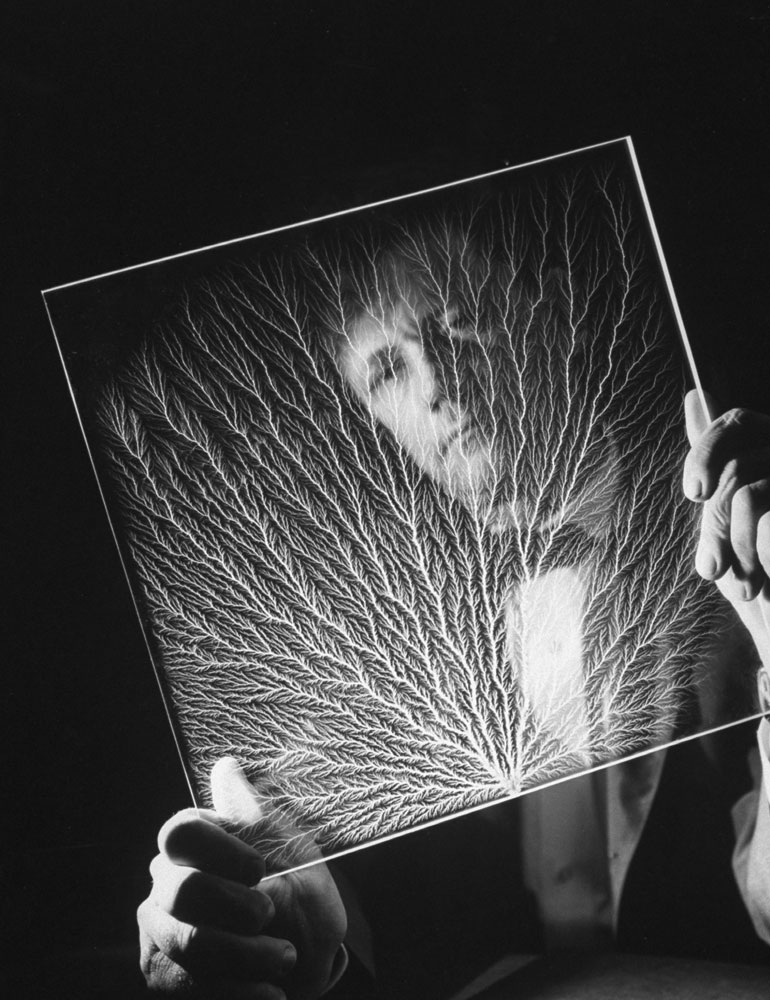 A scientist holds a plastic block that he blasted with charged electric particle while investigating the notion of lightning as a rain trigger, 1962.