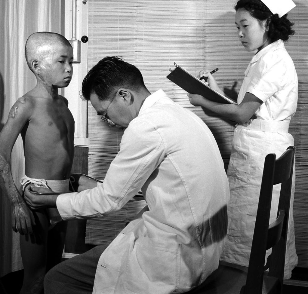 A boy badly burned by the Hiroshima bomb four years earlier is checked by a pediatrician in 1949.