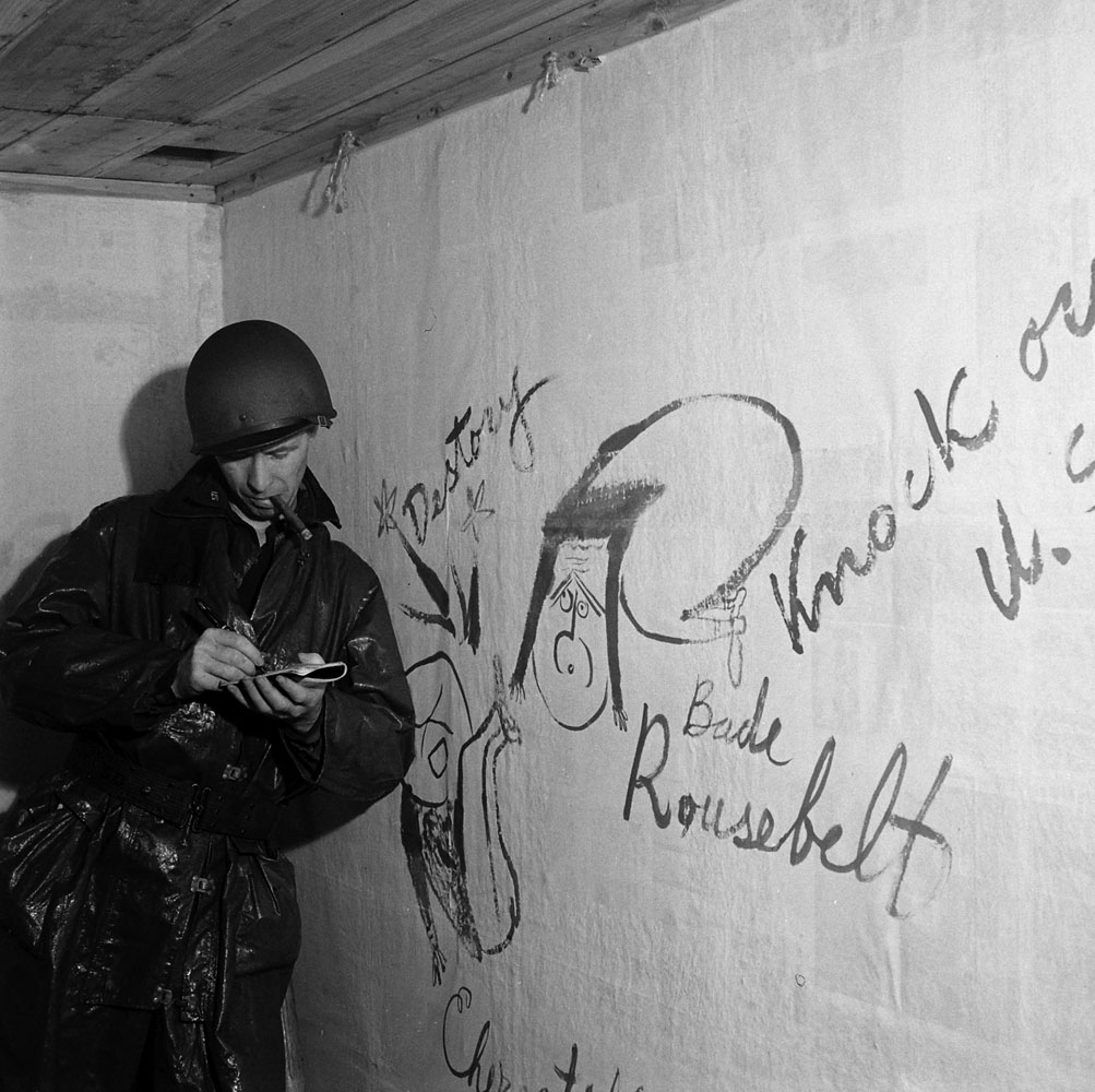 An American soldier leans against a wall in the captured Japanese headquarters on Kiska Island, beside graffiti caricatures of FDR and Churchill (left), 1943.