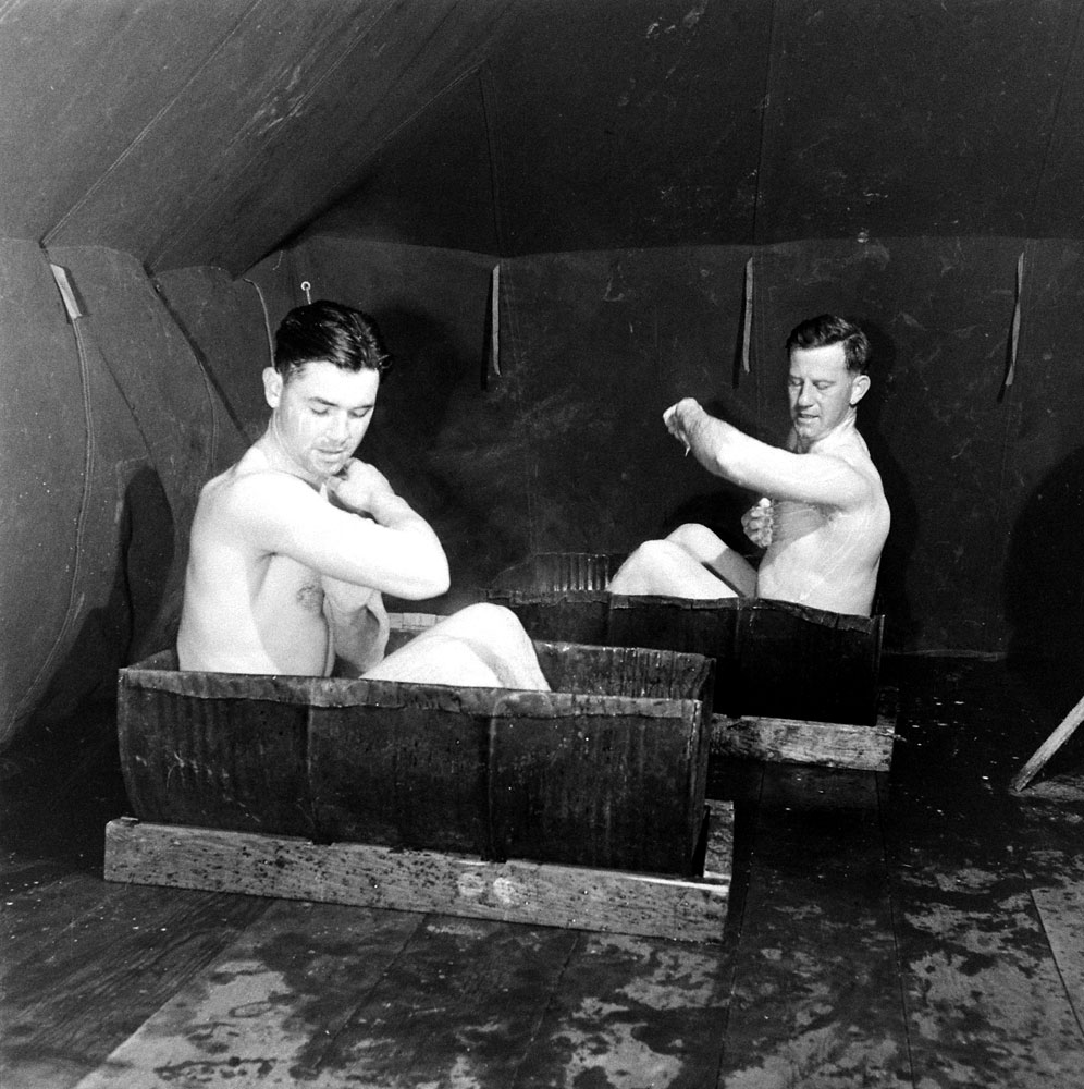 Bathing in halved oil drums, Amchitka Island, Aleutian Campaign, Alaska, 1943.