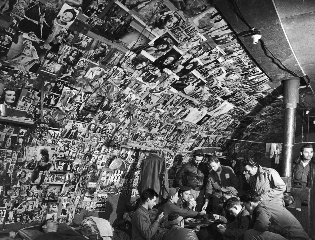 Pin-up photos adorn the walls of a bomber-crew shack on Adak Island, Aleutian Campaign, Alaska, 1943.