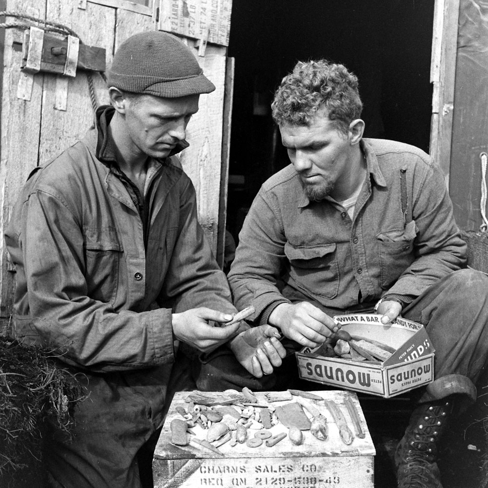 American troops study stone and bone implements and other objects recovered from an earlier settlement, Aleutian Islands Campaign, Alaska, 1943.
