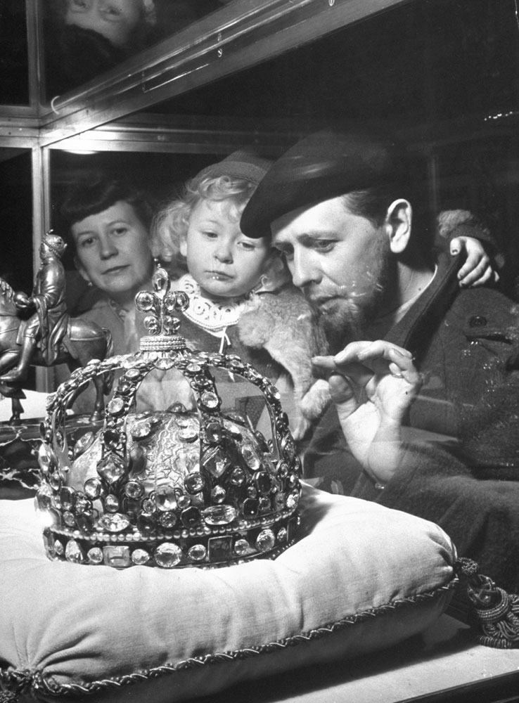 Married couple and their young daughter view the crown of King Louis XV at the Louvre, 1953.