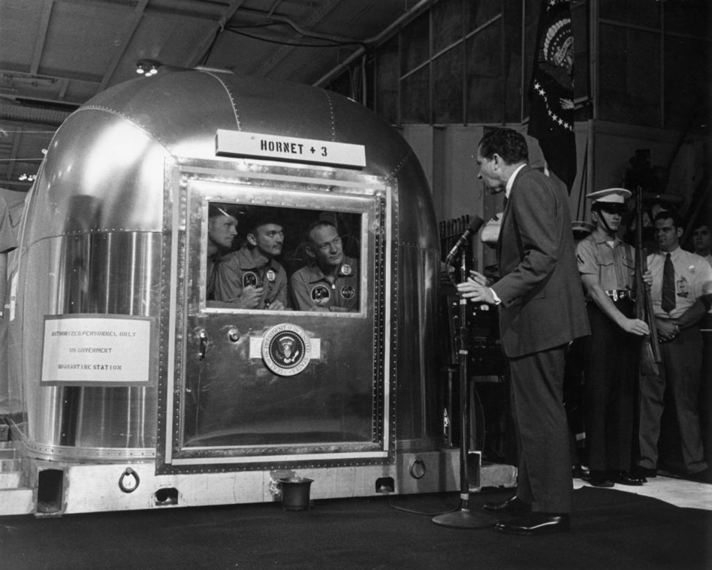 President Richard Nixon speaks with Apollo 11 astronauts Armstrong, Collins and Aldrin (still in their quarantine room) aboard the recovery ship Hornet following the crew's return to Earth, July 24, 1969.