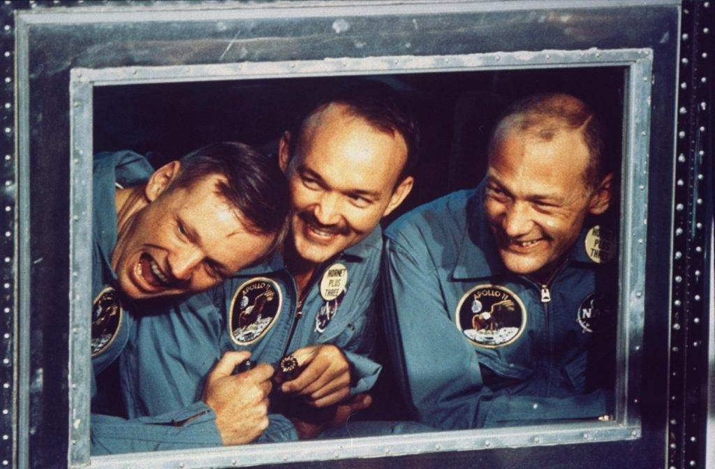 Apollo 11 astronauts Armstrong, Collins and Armstrong peer out the window of their quarantine room aboard the recovery ship Hornet following their return to Earth after historic mission to the moon, July 24, 1969.