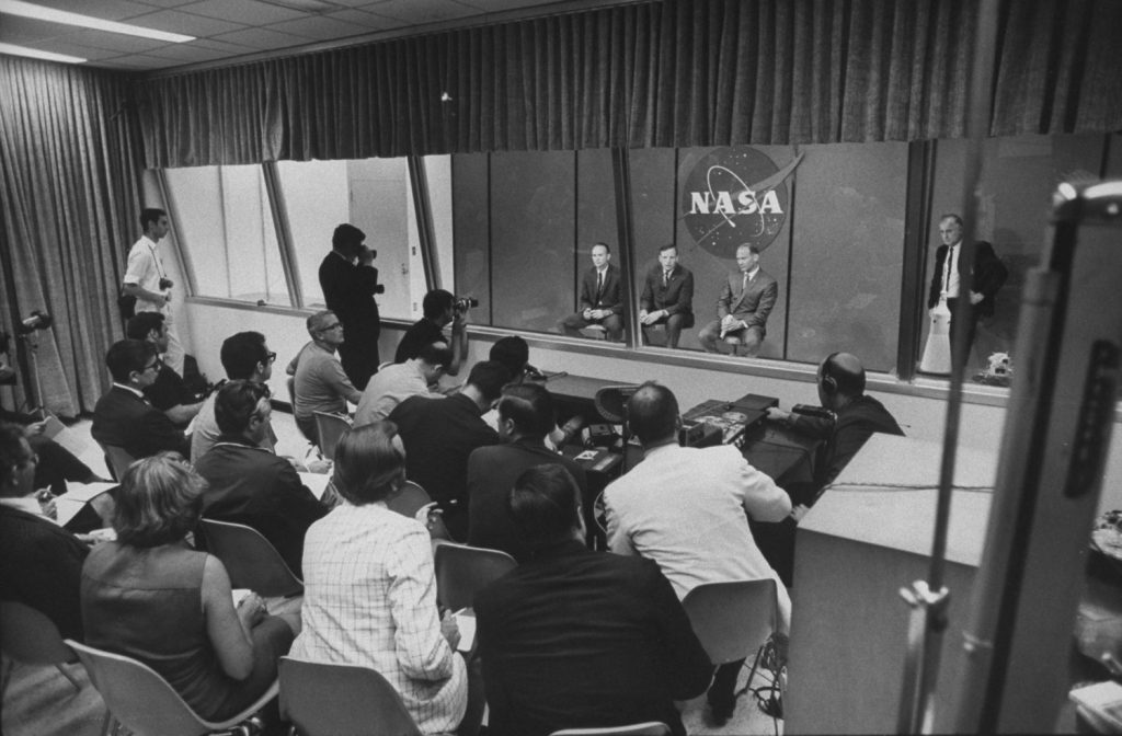 Collins, Armstrong and Aldrin inside a glass-enclosed cage to preserve their post-mission quarantine, July 1969.