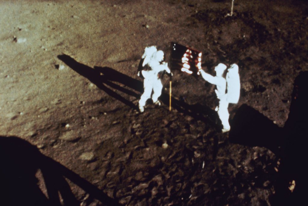 Apollo 11 astronauts Neil Armstrong and Buzz Aldrin plant the American flag on the moon, July 1969.