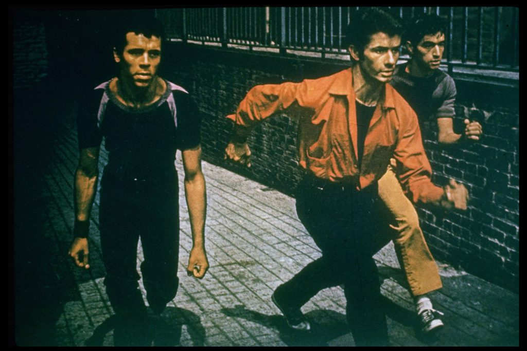 Bernardo (George Chakiris, center) leads gang, the Sharks, in a finger-snapping, crouching invasion of the turf of their rivals, the Jets.