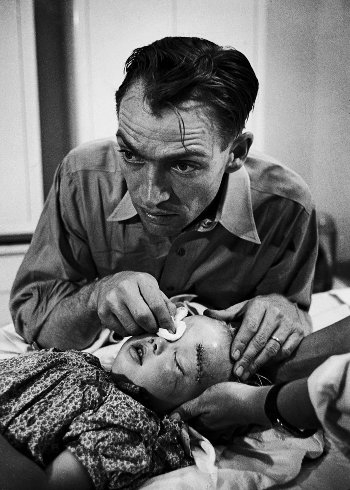 An intensely concerned Dr. Ernest Ceriani holds a bandage on the eye of a young girl whose head he has just stitched up after she was kicked by a horse, Colorado, 1948.