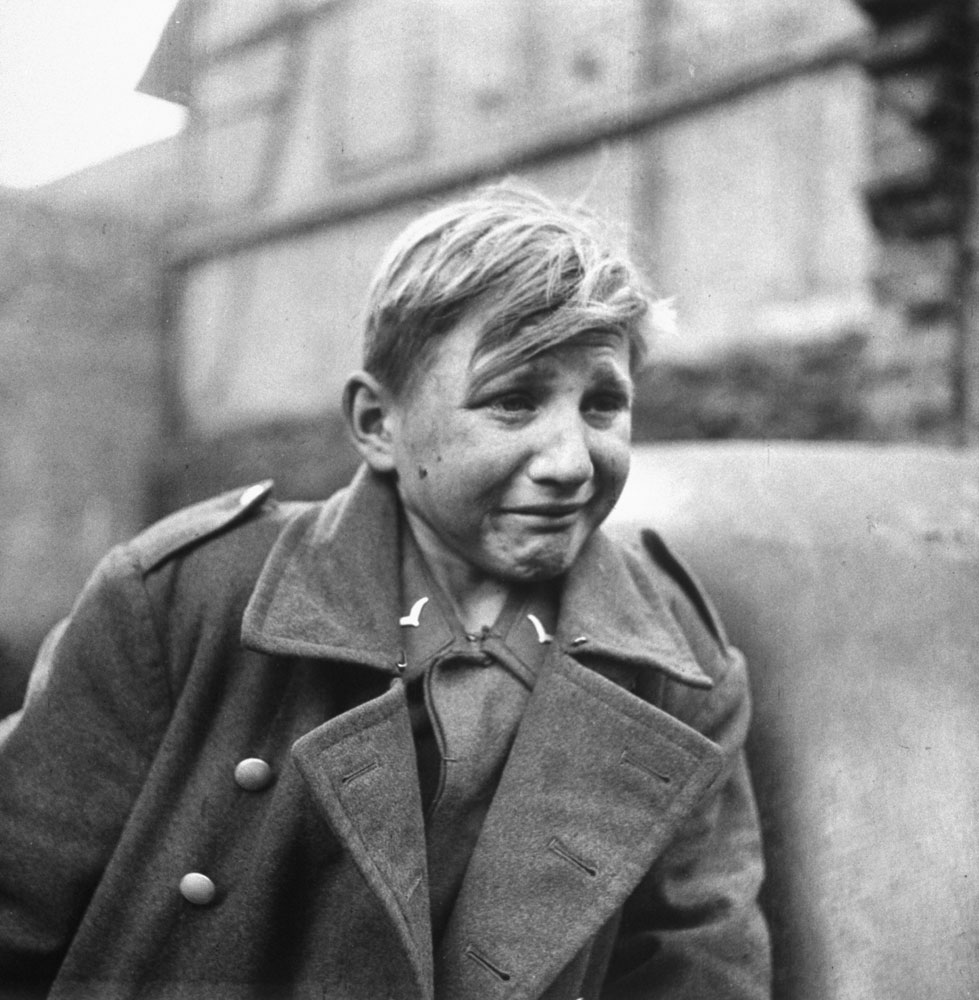 A fearful 15-year-old German Luftwaffe anti-aircraft crew member weeps after being taken prisoner by American forces during the drive into Germany in 1945.