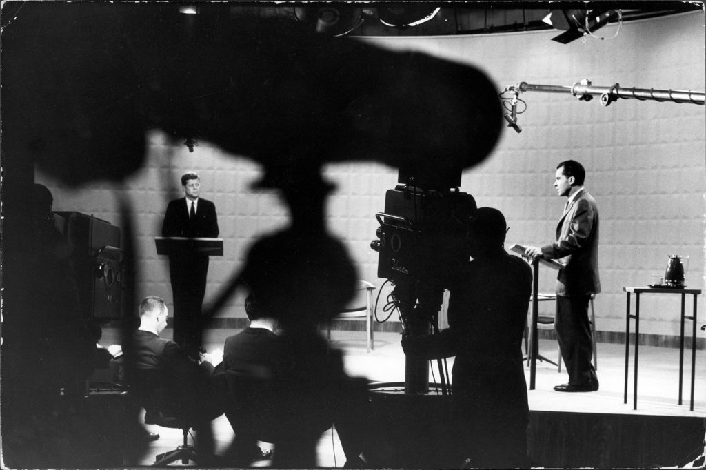 (Left to right) Presidential candidates Sen. John Kennedy and Richard Nixon stand at lecterns as moderator Howard K. Smith presides at first debate, 1960.