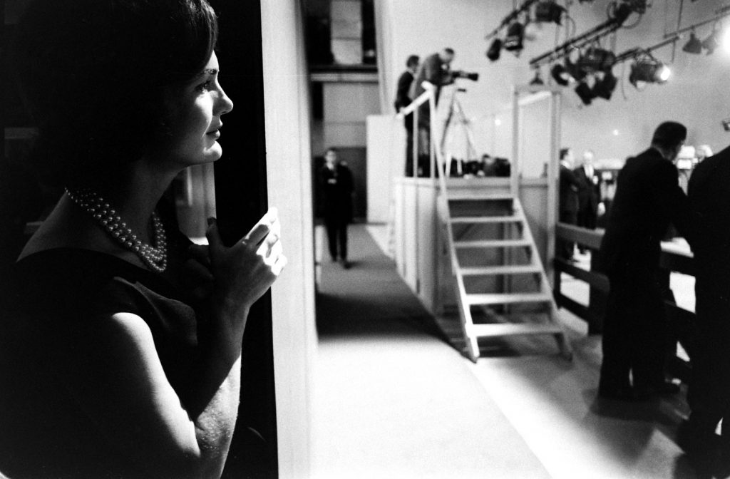 Jackie Kennedy watches from the wings as her husband debates Richard Nixon, 1960.