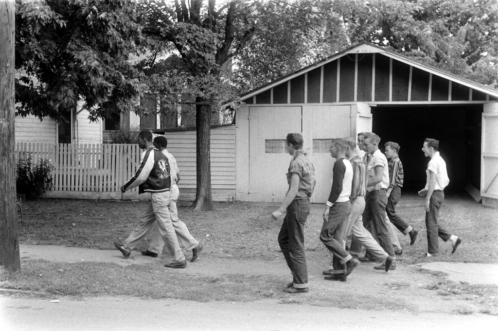 A group of jeering anti-integrationists trail two black students down a street in Little Rock, Arkansas, 1957.